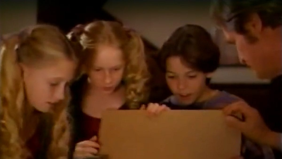 VR.5 - A young Sydney, Samantha, and Duncan look into a box that Mr Bloom is holding open