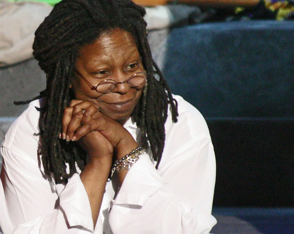 Whoopi Goldberg sitting, wearing a white blouse
