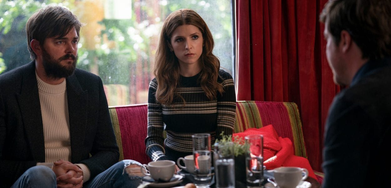 Magnus and Darby (Nick Thune and Anna Kendrick) sit across the table from a man whose back is facing us.