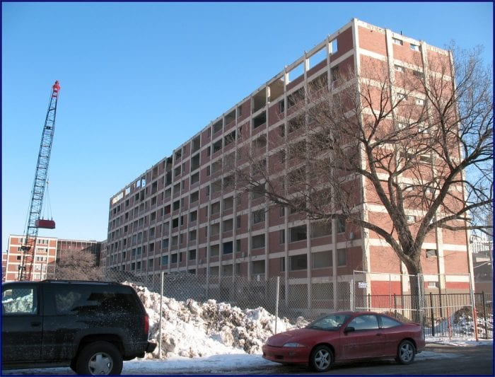 Photo of the Cabrini-Green Housing Complex in disrepair with a crane next to the building