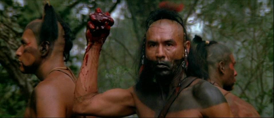 Magua holds up the heart of his enemy, his face and chest are painted in black and he is wearing a feathered head dress