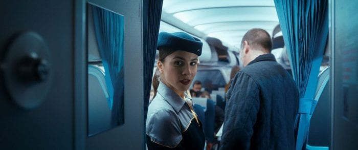 Flight attendant Gökce looks over at Tobias in the cockpit.