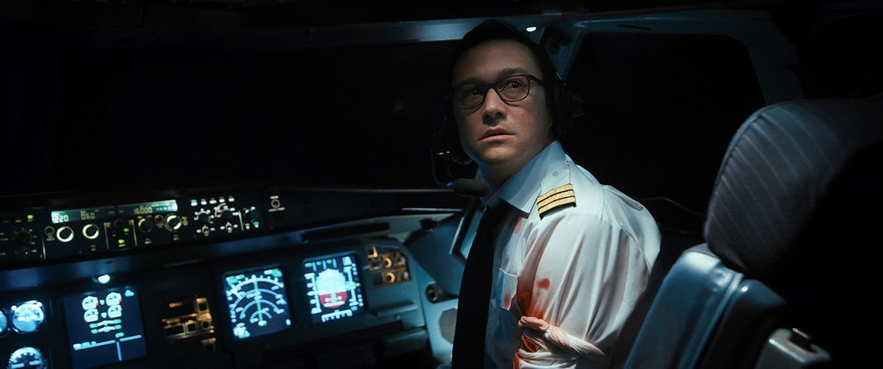 Co-pilot Tobias Ellis looks backward to the seating area monitor in distress from his cockpit seat.