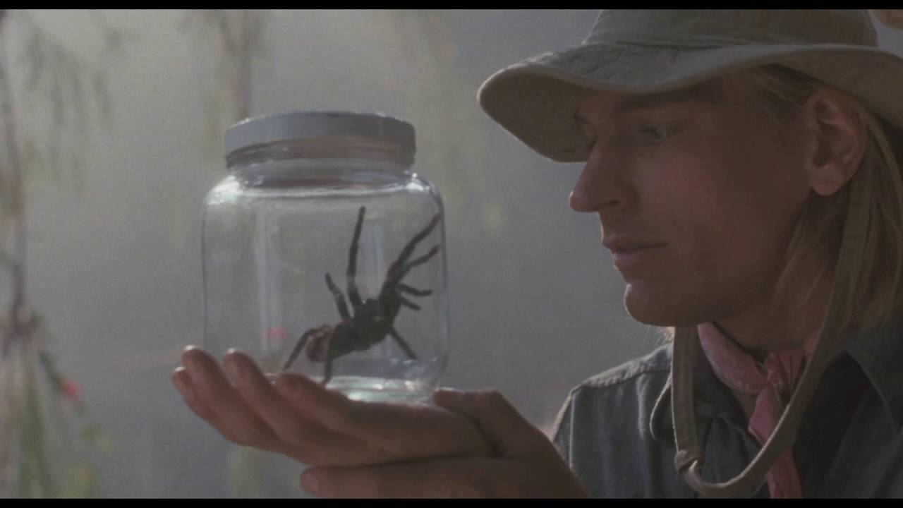 Dr. James Atherton (Julian Sands) examines a spider in a jar.