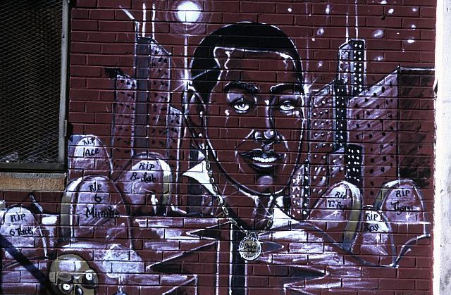 Street art, on a red brick wall, of a black man surrounded by buildings and headstones.