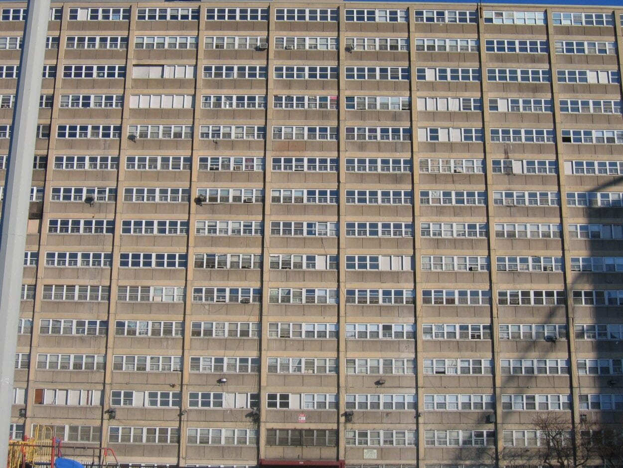 Image full of rows of windows separated by cement columns in housing project.