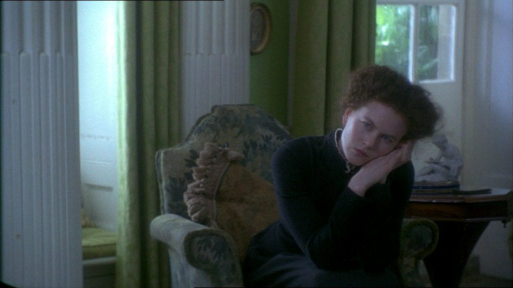 Isabel Archer (Nicole Kidman) sits in a chair, leaning on her hands in The Portrait of a Lady