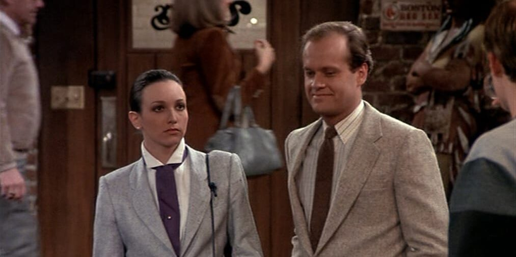 Frasier and Lilith stand at the bar, Lilith glares at the bartender