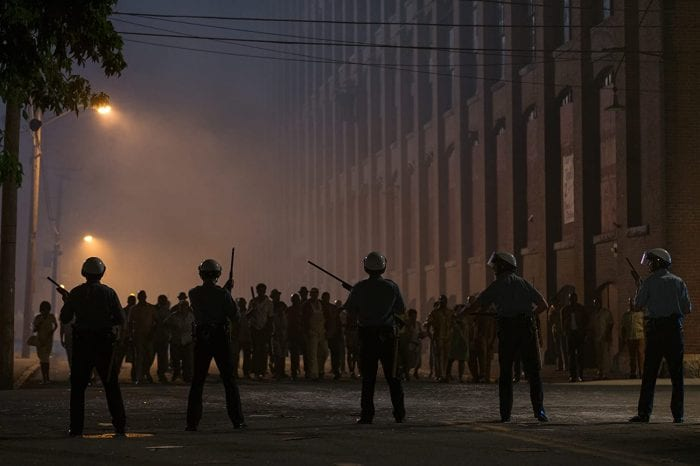 Police and rioters are seen in silhouette against the street lamps at night.