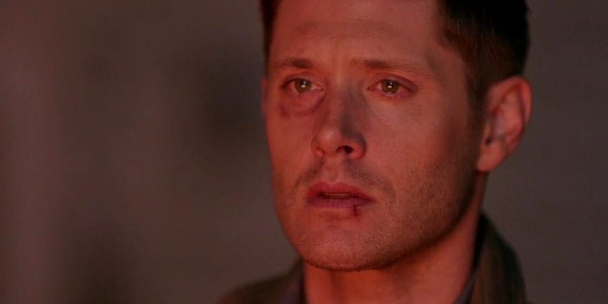 Dean looking distraught in Supernatural with a split lip and bruised eye