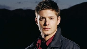 Dean Winchester from Supernatural staring intensely at camera wearing a grey jacket and red shirt