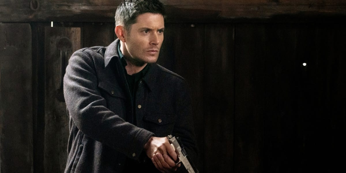 Dean Winchester looking angry and intense holding a gun in his hands in Supernatural