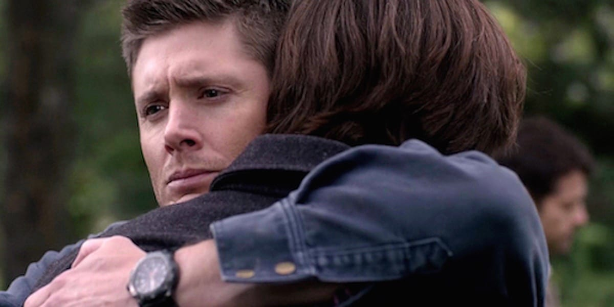 Dean hugging Sam with a sad and relieved look on his face in Supernatural