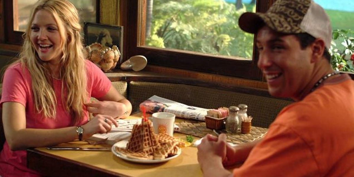 Drew Barrymore and Adam Sandler in 50 First Dates sitting at a table with a waffle tower in the center, both are looking to the side and smiling
