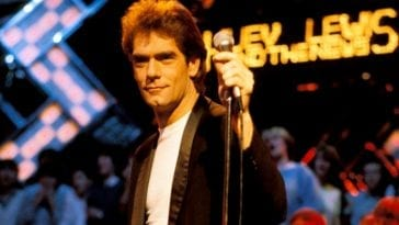 Huey Lewis with one hand on the microphone and a neon advertising his band's name in the background among other neon lights