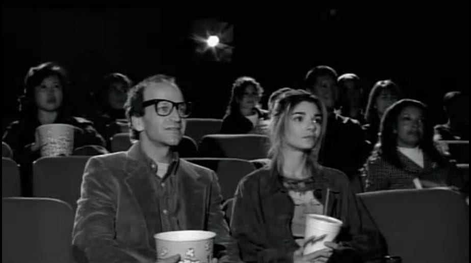 Maya sits in a movie theater with the fake Woody Allen, holding concessions