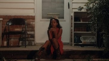 Turquoise Jones sits on her porch wearing a dress, cowboy boots, and her old Miss Juneteenth tiara.