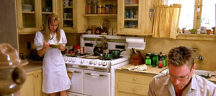 Betty stands in her kitchen away from Del on her birthday