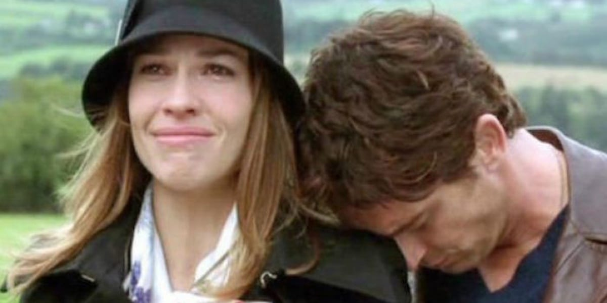Hilary Swank looking into the distance, smiling yet teary-eyed, with Gerard Butler leaning his head on her shoulder in PS I Love You