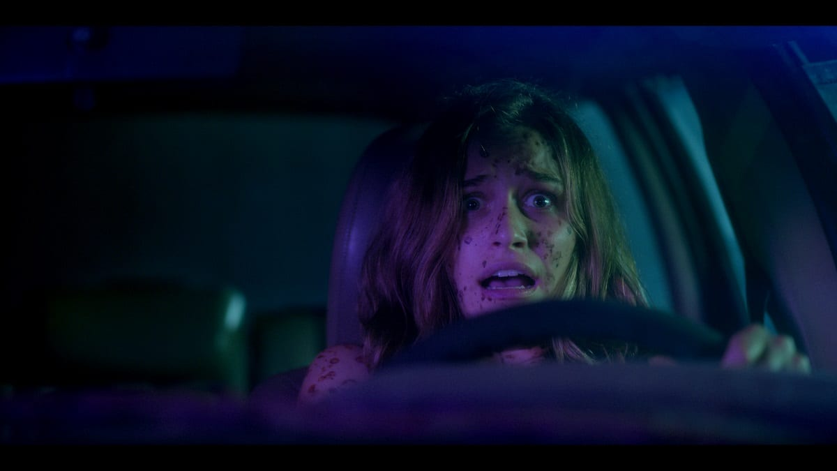 Jesse sits in the car with blood on her face, gripping the steering wheel with a frightened look on her face..