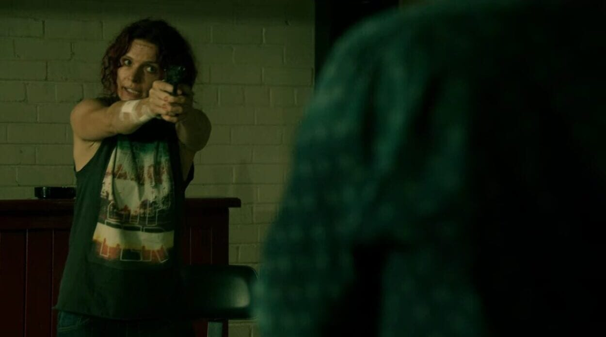 Bea (Danielle Cormack) holds Brayden Holt (Reef Ireland) at gunpoint in a scene from Wentworth.