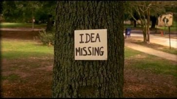 "A shot of a tree with a sign that says ""Idea Missing"" in bold letters"