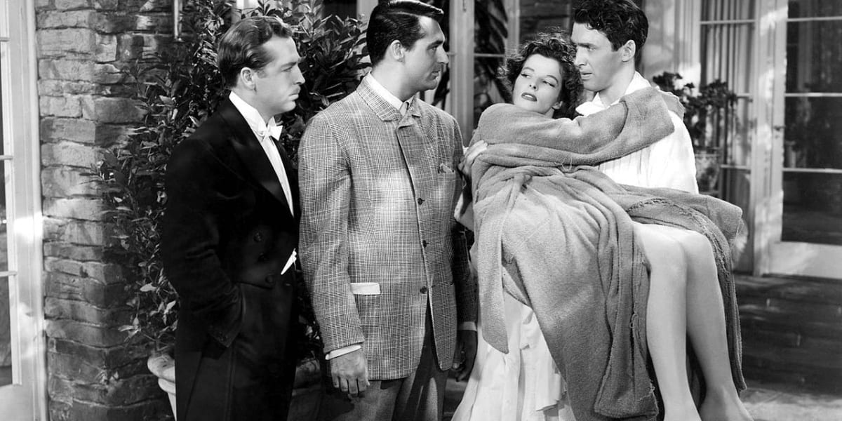 John Howard and Cary Grant stand to the left, looking at Jimmy Stewart sternly as he holds a dazed-looking Katharine Hepburn in his arms in black and white in The Philadelphia Story