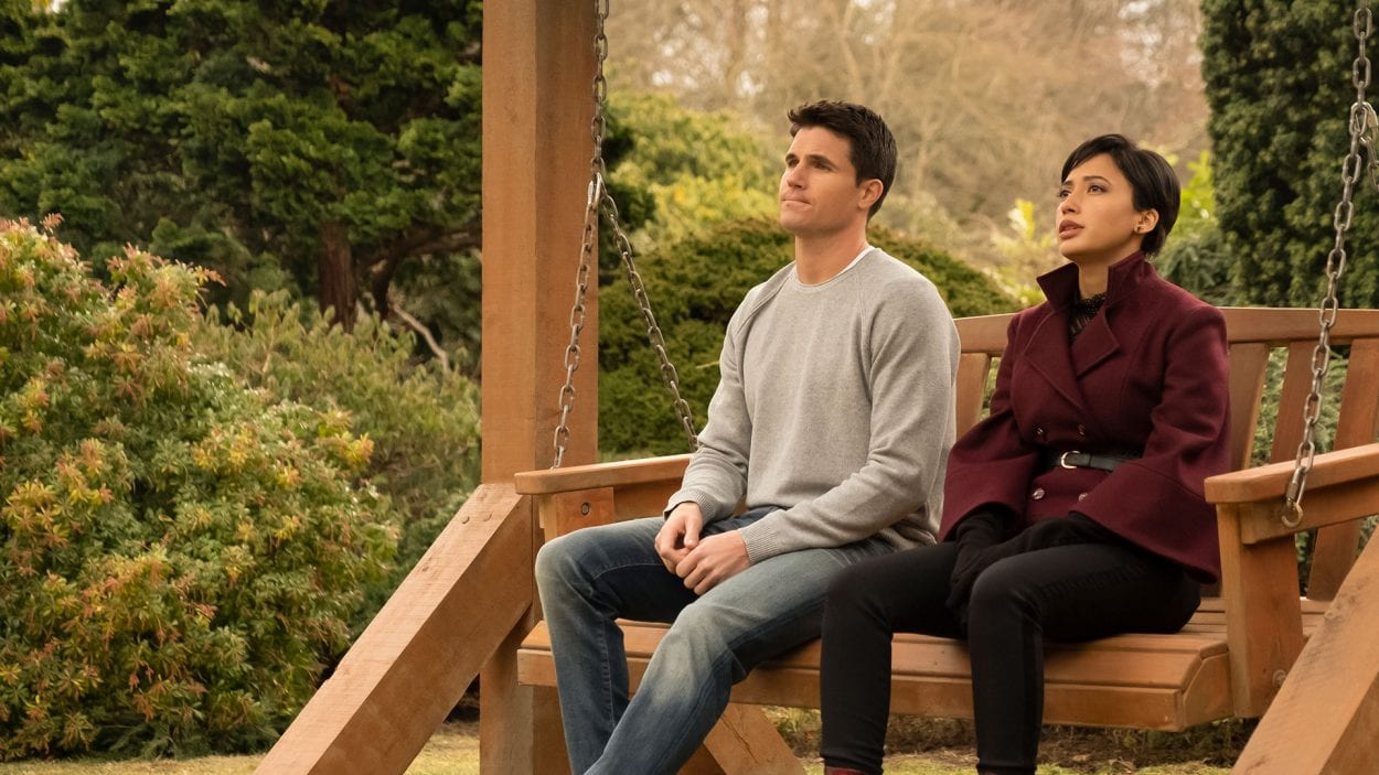 Nathan and Nora (Robbie Amell and Andy Allo) sit on a swing while looking off into the distance.