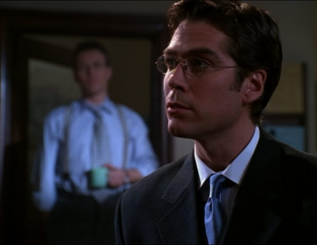 Wesley is giving advice in Sunnydale High Library while Giles looks on