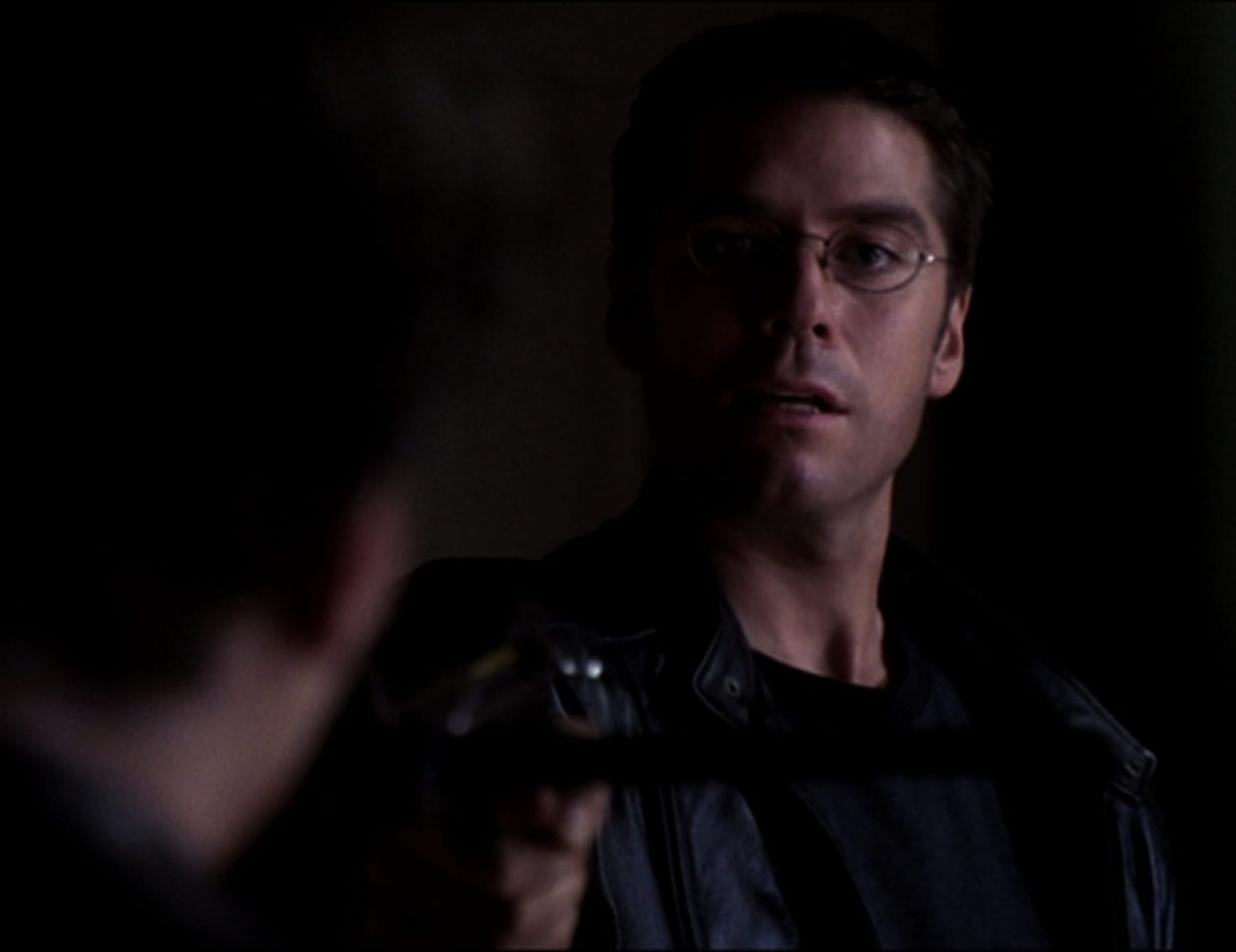 Wesley, wearing a leather jacket, points a crossbow at Angel
