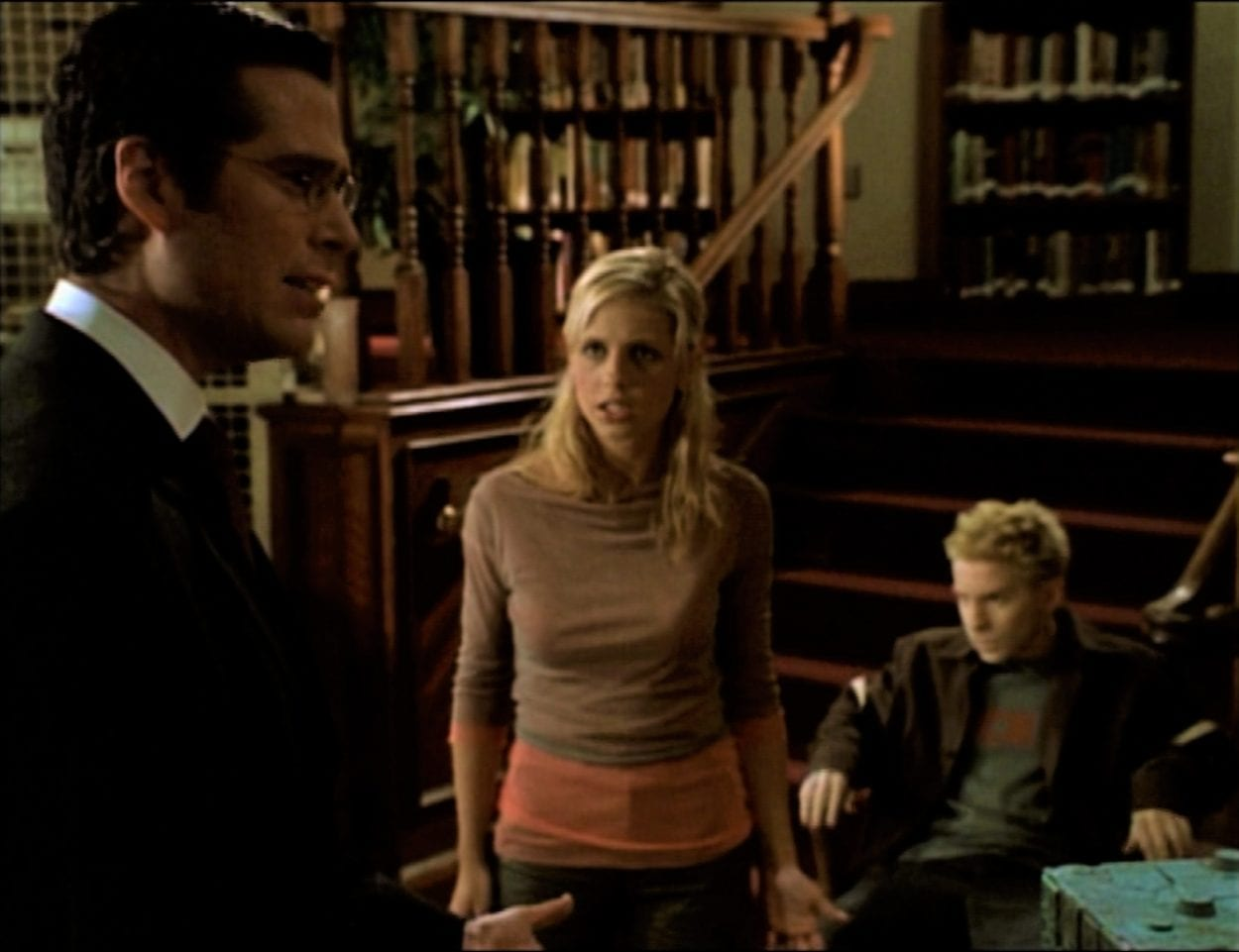 Wesley and Buffy are arguing in the library, while Oz sits in the background