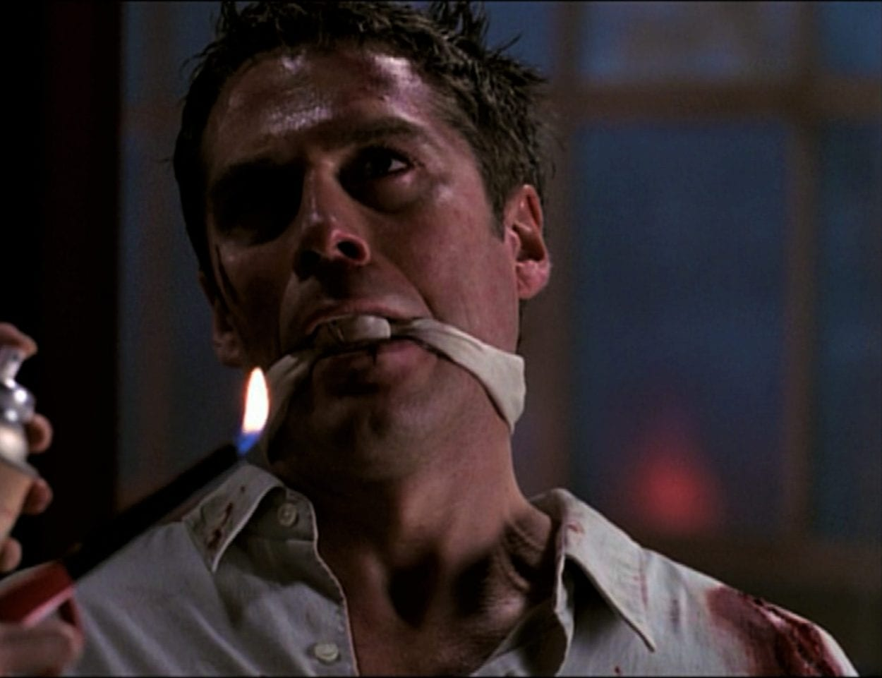 Wesley is gagged and bloody, while Faith prepares to burn him