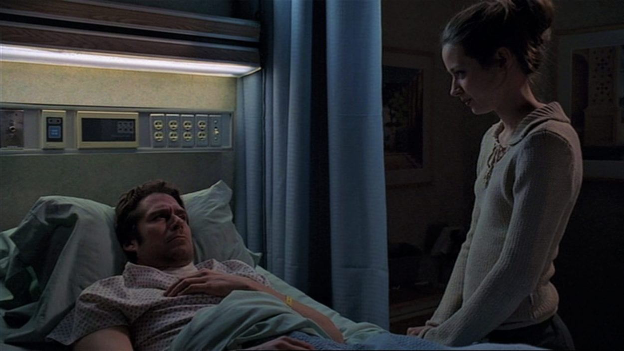 Wesley lies in a hospital bed with his throat bandaged as Fred stands next to him