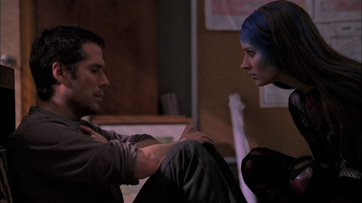 Wesley sits on the floor and Illyria crouches in front of him
