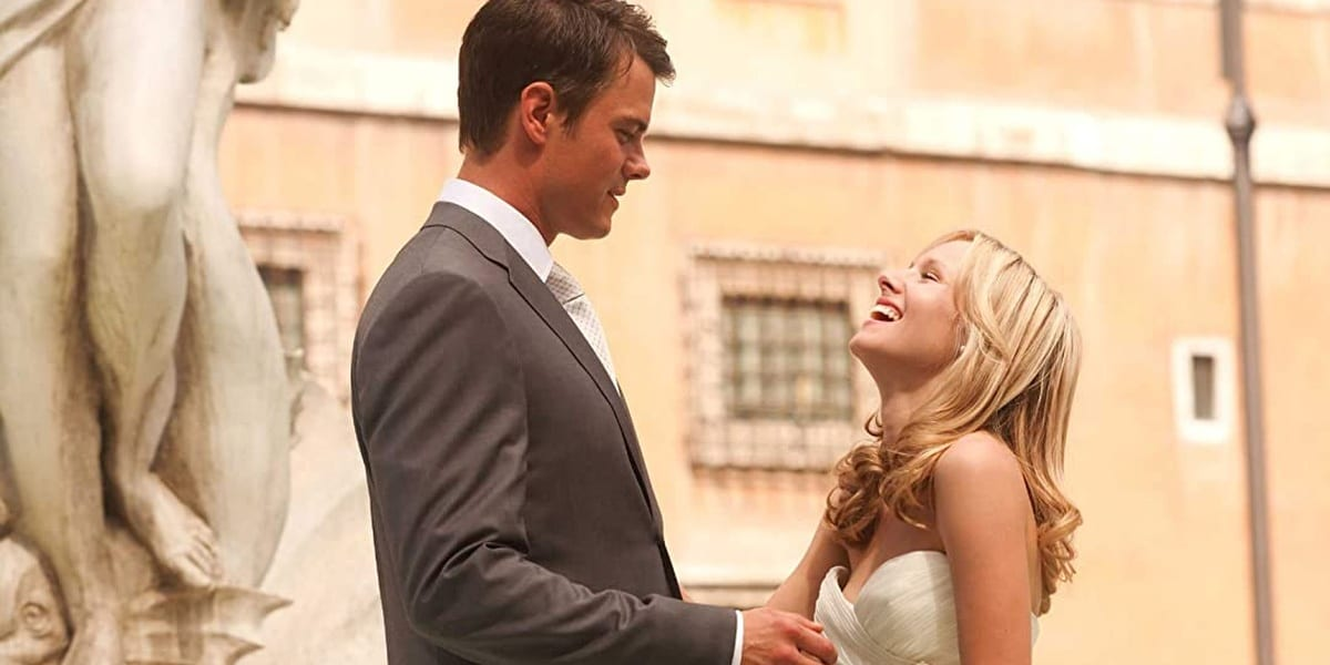Josh Duhamel looking down at Kristen Bell as she looks up at him laughing and eyes closed in When In Rome dressed for their wedding