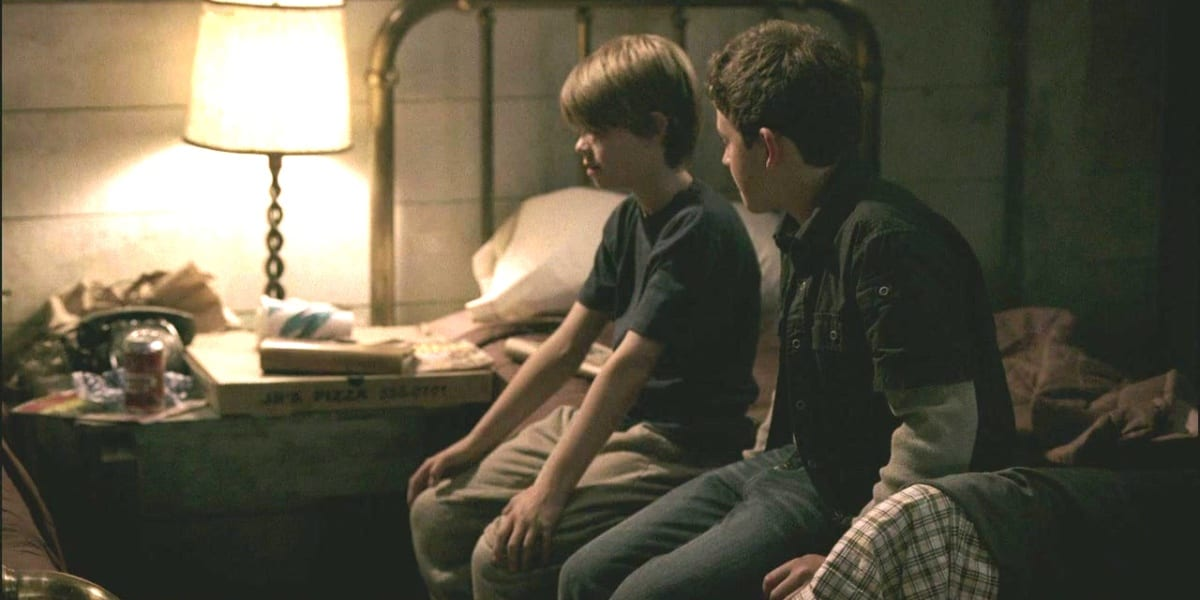 Young Sam and Dean sitting on a bed, Sam looking down and Dean looking at Sam, with one lamp lit in a dark motel room in Supernatural