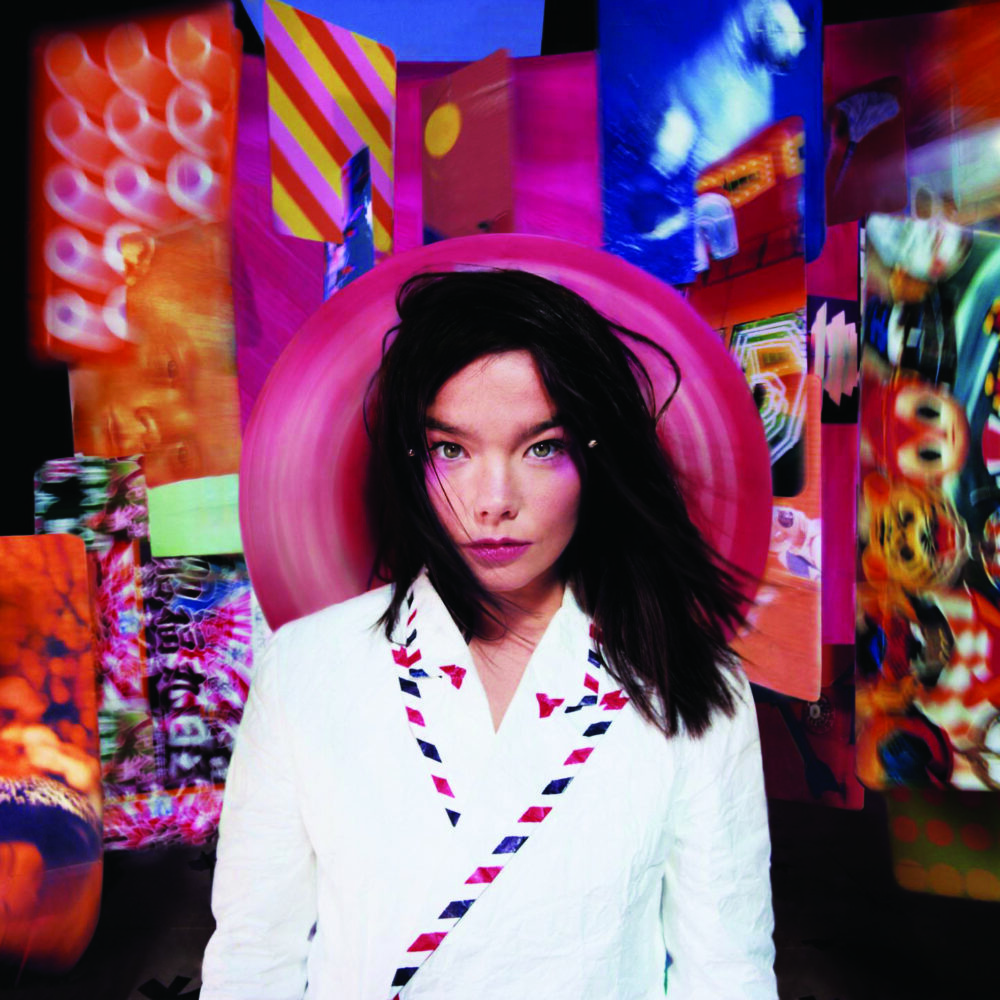 Bjork's face and black hair stick out from her white robe. Behind her is an abstract collage in purples, oranges and blues.