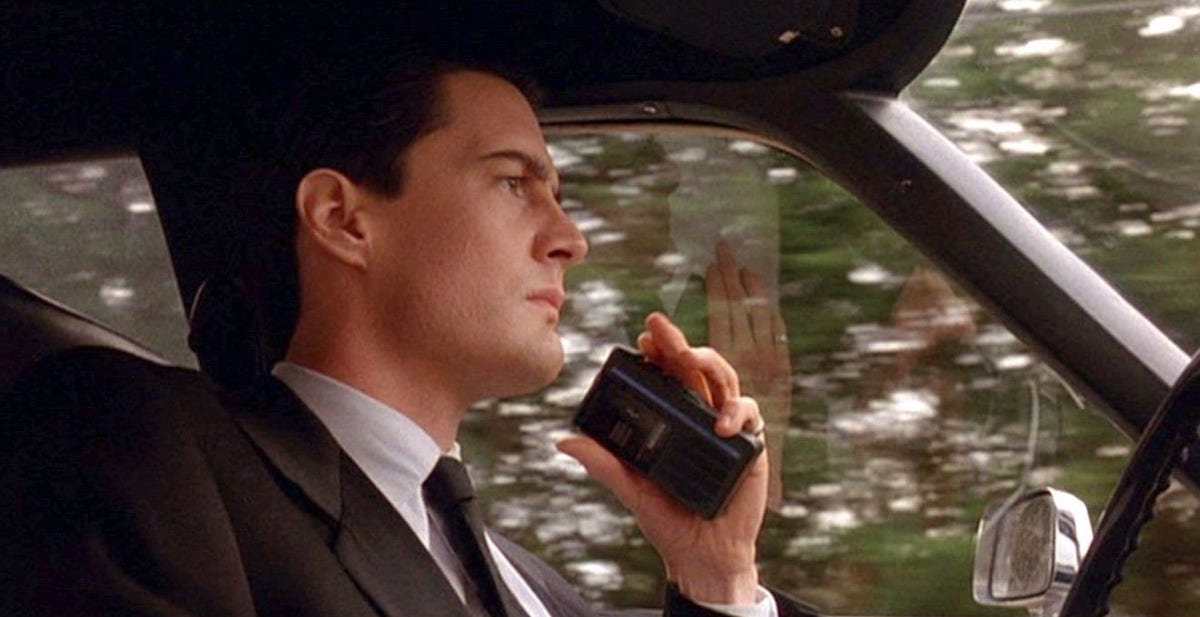 Agent Cooper holds his tape recorder in the car on his way into Twin Peaks