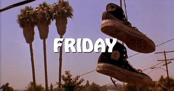 a pair of shoes hang over a telephone wire with the word Friday on the screen
