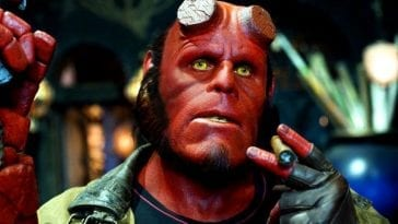 A close up shot of Hellboy with his Samaritan pistol on his left hand and a lit cigar in his right