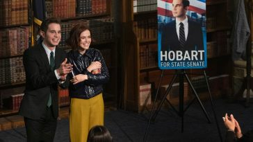 Payton and Infinity (Ben Platt and Zoey Deutch) stand in front of an audience during a speech for Payton's State Senate campaign.