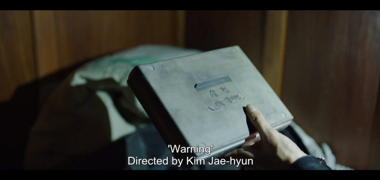 close up of a video cassette with a title sticker written in Korean being held by a female hand while a phone light shines on it - subtitles indicate the label reads - Warning, directed by kim jae-hyun