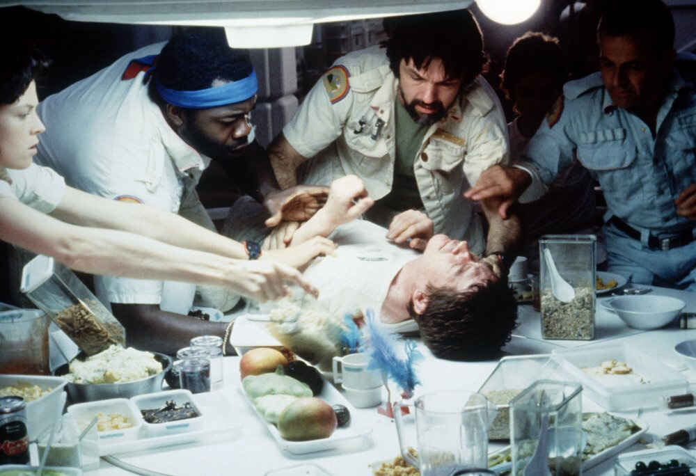 A group of scientists crowd around a sickly man on a table with various specimens and tools on the table in the foreground.