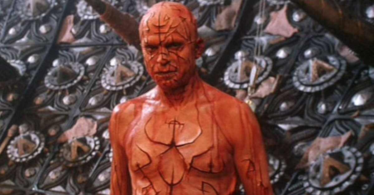 A shirtless man with symbols carved into his face and body.
