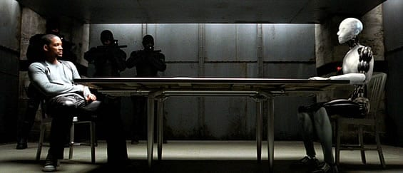 Detective Spooner sits across from Sonny in an interrogation room with armed guards in the background pointing assault rifles in Sonny's direction