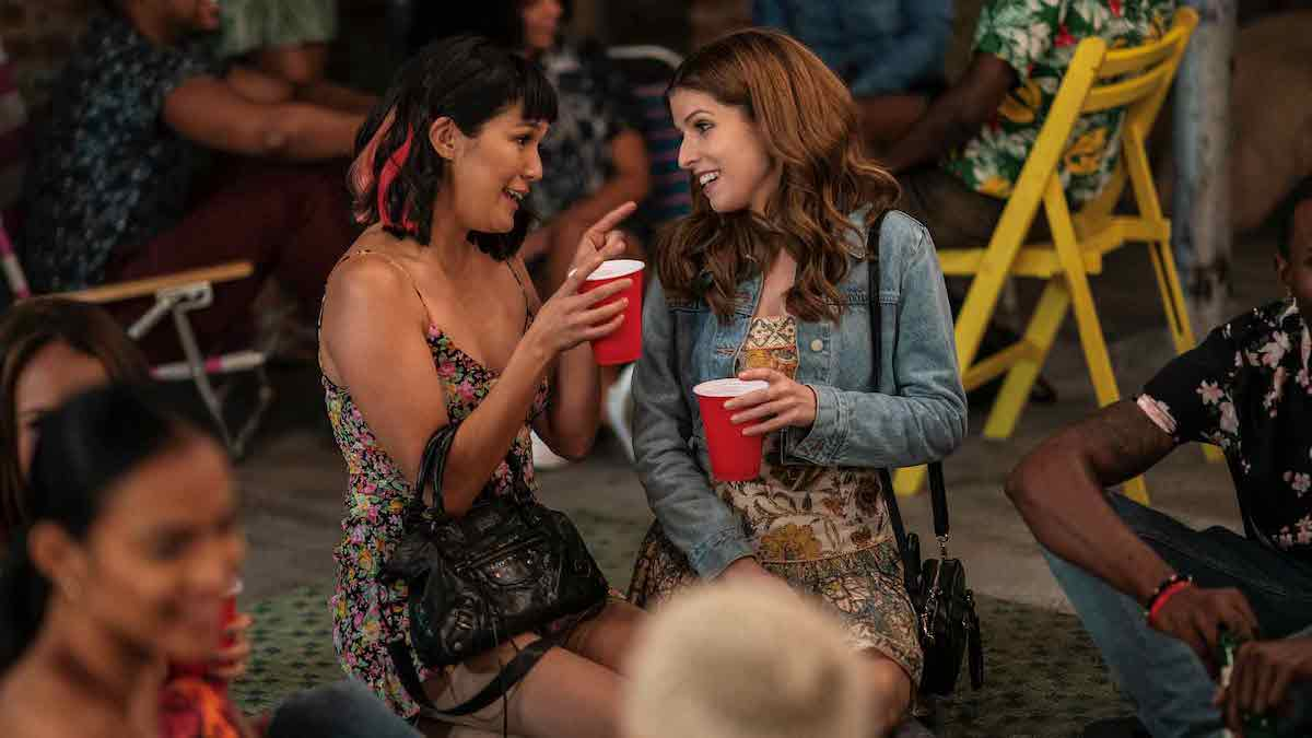 Best friends Sara and Darby are at a party holding red solo cups and talking to each other.