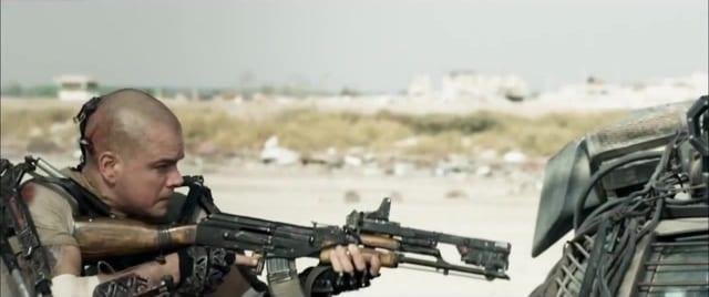 Max Da Costa stands in cover behind a car with a modified AK-47 drawn