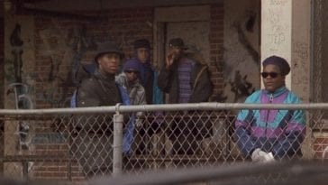 Five young black males stand behind a chain-link fence near a housing complex