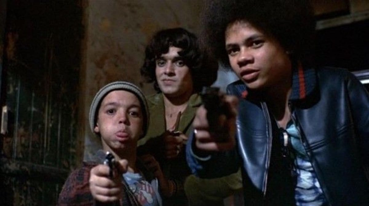 Pixote (Fernando Ramos da Silva) and Dito (Gilberto Moura) aim their weapons to rob Sueli's (Marília Pêra) offscreen customer with Lilica (Jorge Julião) standing behind them.