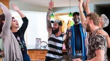 The Queer Eye crew raises hands in the air